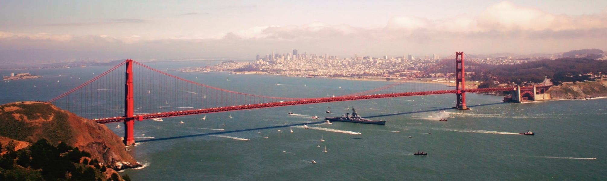 Golden Gate Bridge, with USS Iowa passing through